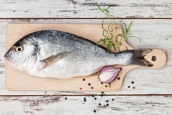 14886299 - delicious fresh sea bream fish on wooden kitchen board with onion, rosemary and colorful peppercorns on white textured wooden background  culinary healthy cooking