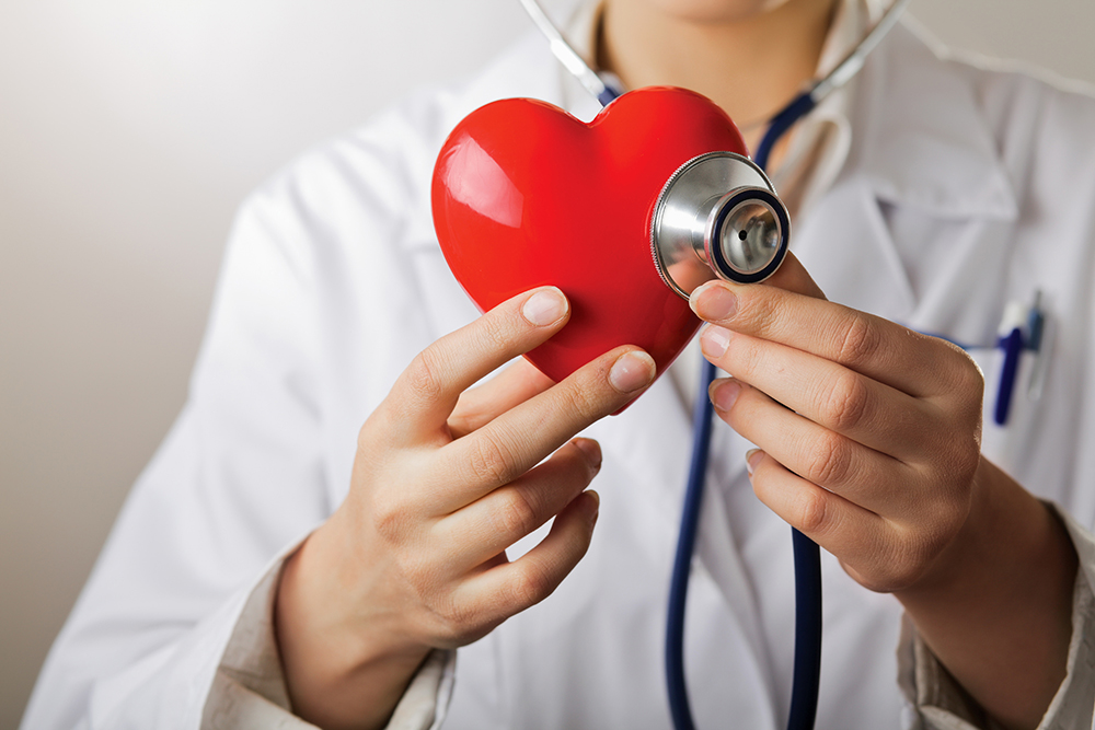 A doctor with stethoscope examining red heart